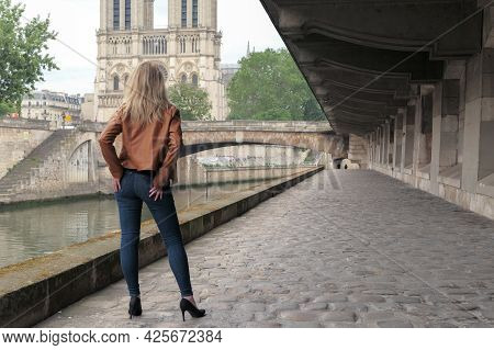 Blonde Woman In Trousers, Standing From Behind On The Banks Of The Banks Of The Seine. Cathedral Of