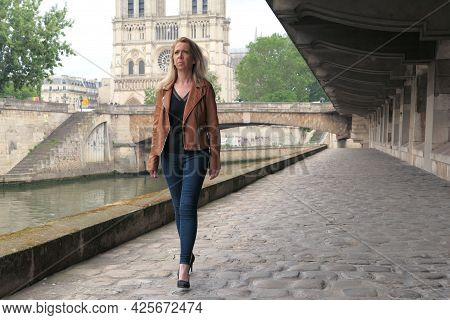 Beautiful Fashionable Blonde Woman With A Brown Jacket And High Heels, Walking On The Cobblestones O