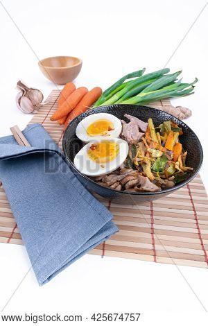 Vertical, Wide Studio Shot Of Black Bowl Of Ramen Noodles With Boiled Eggs, Veggies And Turkey Meet,