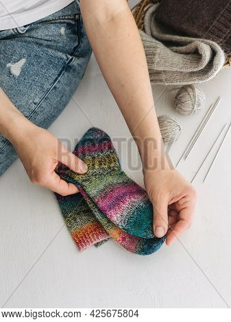 Woman With Hand Knitted Sokcs, Needles And Yarn Balls In A Basket On A White Background. Concept For