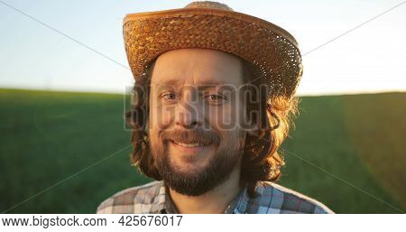 Portrait Of Positive Middle-aged Farmer Staying In Planting Or At The Field And Smiling To The Camer
