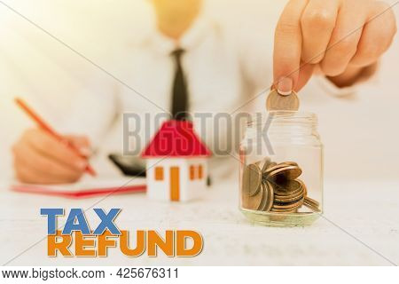 Hand Writing Sign Tax Refund. Word Written On Excess Payment Of Paid Taxes Returned To Business Owne