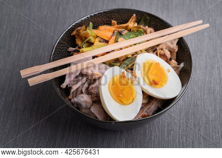 Black Bowl Of Ramen Noodles With Boiled Eggs, Veggies And Turkey Meet, Ready To Be Poured With Boili