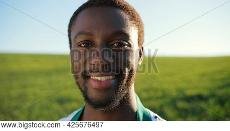 Portrait Of Positive Middle-aged Multiracial Farmer Staying In Planting Or At The Field And Smiling