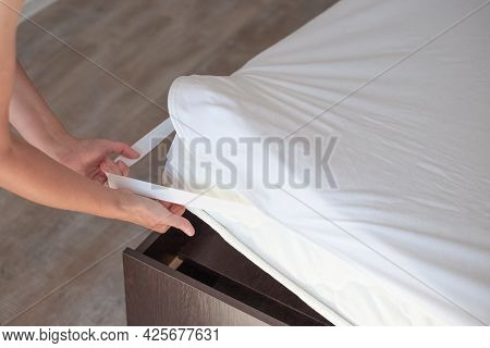 Bed With A High Mattress. The Woman Puts On A Protective Water-repellent Mattress Cover.