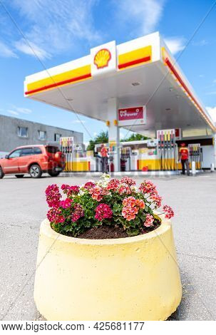 Samara, Russia - July 2, 2021: Flowers Against The Blured Image Of Shell V-power Fuel Station. Selec