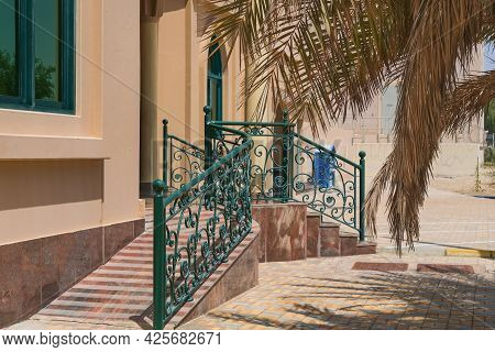 Front Elegant Porch With Ornate Forged Floral Design Railings With Staircase And Gentle Ramp For Eas