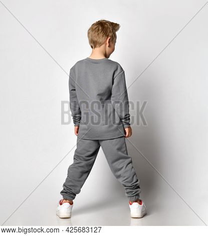 Small Blond Boy With A European Appearance In Trendy Sportswear, Standing Backwards And Looking To T