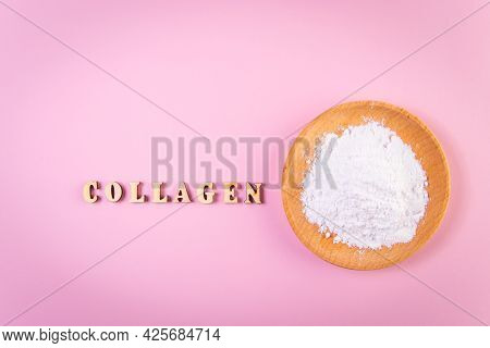 Collagen Powder In Wooden Bowl On Pink Background. Natural Bio Supplement For Skin, Bone And Joint H