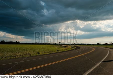 A Two-lane Road Curves Into The Distance As It Passes By Farm Fields Under Dramatic Clouds Of A Comi