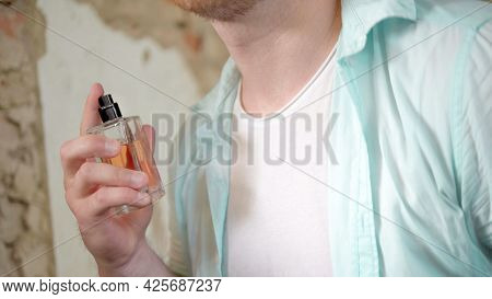A Man Uses Perfume, A Man With A Masculine Perfume In His Hands.