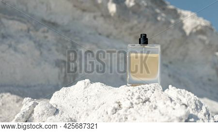 A Bottle Of Men's Perfume With A Copy Space, Eau De Toilette On The Background Of A White Mountain