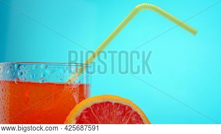 Orange Juice In A Transparent Glass With A Straw. Chilled Lemonade On A Blue Background.