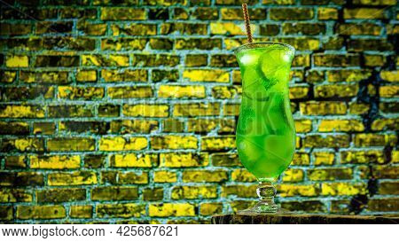 Alcoholic Cocktail In A Glass On A Brick Wall Background. Green Lemonade With Ice. Summer Fresh Drin