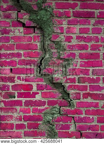 Texture Of A Brick Wall With Cracks In Red. The Destroyed Ancient Wall Is Claret. Brick Background C
