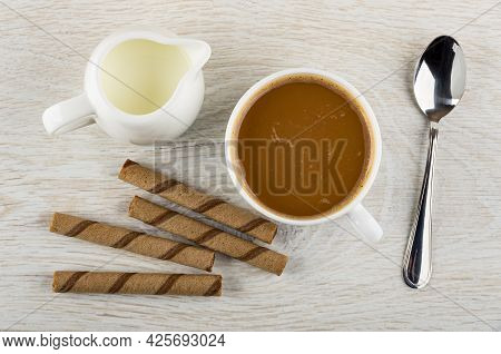 Pitcher With Milk, Brown Striped Wafer Rolls With Chocolate Filling, Coffee With Milk In Cup, Teaspo