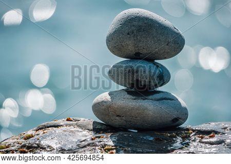 Pyramid Stones On The Seashore On A Sunny Day On The Blue Sea Background. Happy Holidays. Pebble Bea