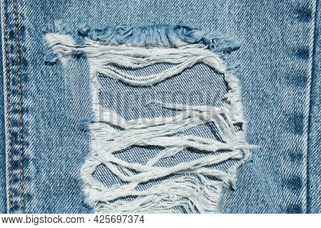 Hole And Threads On Denim Jeans. Ripped Destroyed Torn Blue Jeans Background. Close Up Blue Jean Tex