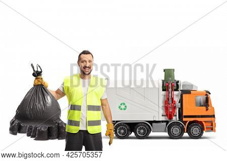 Waste collector holding a bin bag in front of a garbage truck isolated on white background