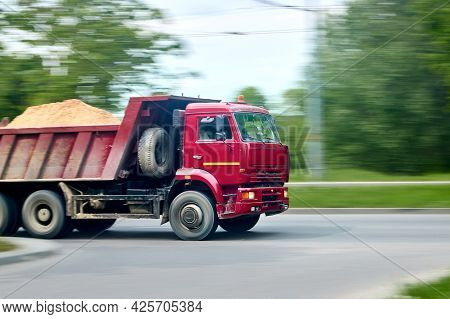 Red Heavy Industrial Dump Truck Lorry With Sand In Back, Panning Blur Shot Moving In City Motion Blu