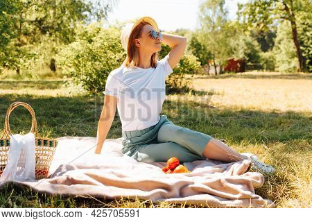 Lovely Young Woman In A Hat And Glasses Having A Rest, Lying On A Blanket In The Summer, Outdoors. B