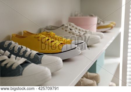 White Shelving Unit With Collection Of Colorful Sneakers Indoors