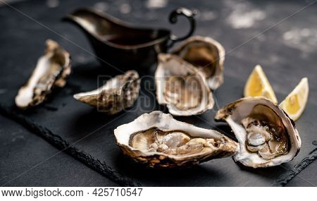 Raw opened oysters served with lemon and sauce on balck platter
