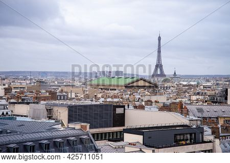 Paris, France, 23 December 2019 - View Of The Eiffel Tower Towering Over The City Roofs Against A Cl