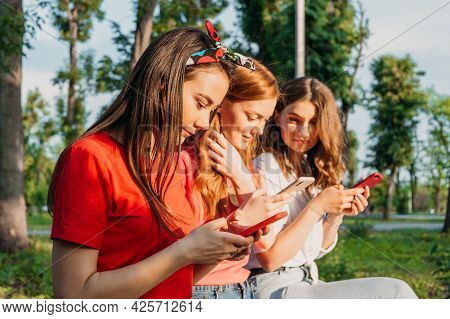 Three Girl Friends Watching Mobile Smart Phones And Having Fun Sitting On Bench In Public Park. Gen