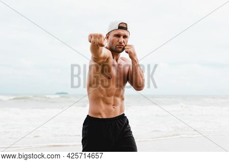 Medium Shot. Portrait Of A Strong Man Boxing Training Outdoor At The Seaside. The Half Naked Male He