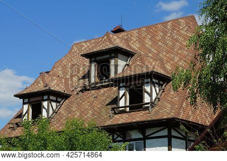 Attic Of An Old Abandoned Private House With An Empty Windows Under A Brown Tiled Roof Against A Blu