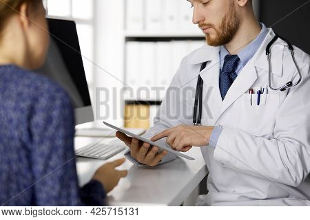 Unknown Bearded Doctor And Patient Woman Discussing Current Health Examination While Sitting And Usi