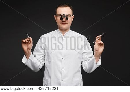 Caucasian Male Doctor In Binocular Loupes Glasses And With Surgeon Equipment At The Black Background