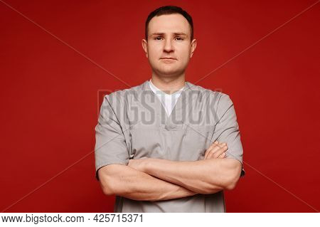 Portrait Of A Male Doctor In Medical Uniform With Crossed Arms Looking At The Camera In The Red Back