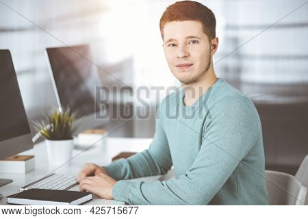 Young Confident Businessman, Wearing A Green Pullover, Is Sitting At The Desk In A Sunny Modern Offi