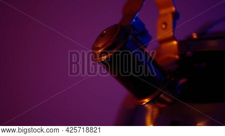Close Up Of A New Steel Metal Kettle Isolated On Pink Wall Background. Action. Household Utensils Co
