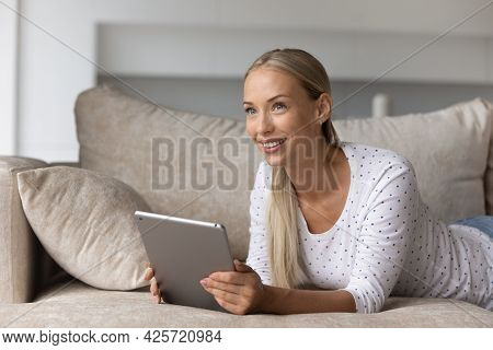Smiling Dreamy Woman Distracted From Tablet Screen Lying On Couch