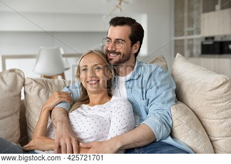 Dreamy Happy Young Couple Hugging, Relaxing On Couch Together