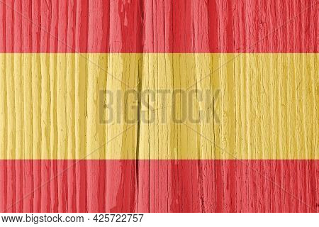 The Flag Of Spain On Dry Wooden Surface, Cracked With Age. It Seems To Flutter In The Wind. Backgrou