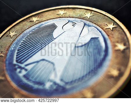 1 Euro Lies On A Dark Surface. The Coin Was Issued In Germany. Obverse With The Federal Eagle. Close