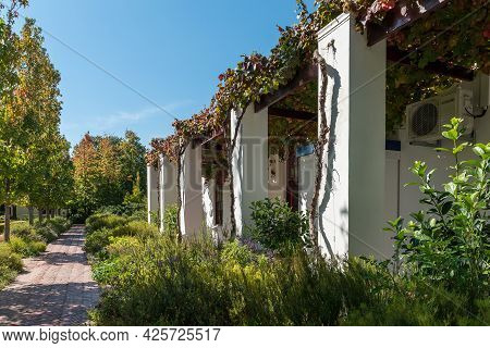 Somerset West, South Africa - April 13, 2021: A Building, With A Vine On A Trellis, And A Path At Lo