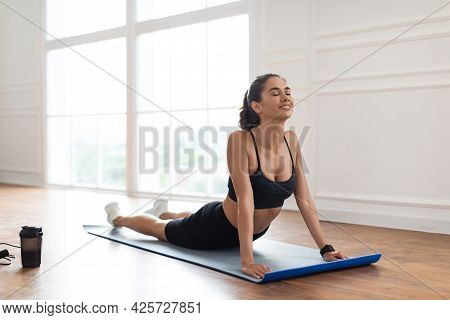 Young Woman Stretching Back On Mat, Cobra Pose