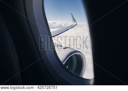 View Through Airplane Window On Wing With Engine. Plane During Flight Above Clouds.