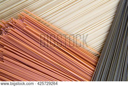 The Long Pasta In Three Colors Is Beautifully Laid Out. Yellow Green And Red Spaghetti Make A Beauti