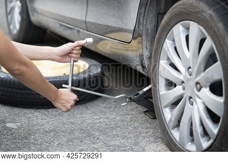 Woman Changing Wheel On A Roadside, Close Up