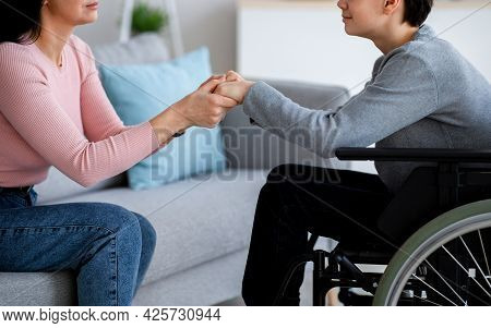 Handicapped Teenage Boy In Wheelchair Receiving Support From His Mother Or Caregiver, Holding Her Ha