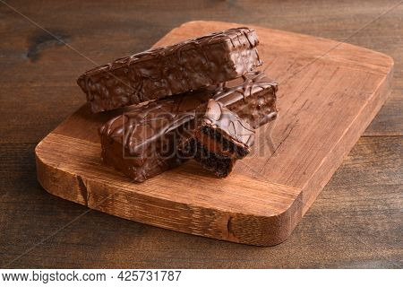 Three Sliced Chocolate Bar Cakes On Cutting Board
