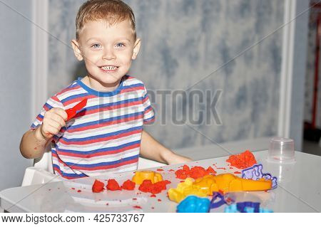 A Cheerful Boy Nibbles On A Toy Knife And Smiles. An Educational Game Of Kinetic Sand With The Use O