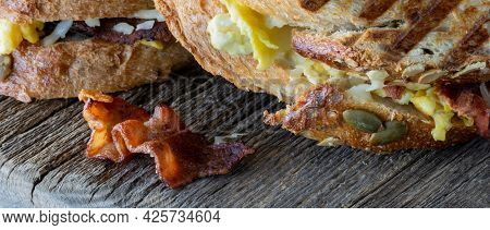 Close Up Of A Piece Of Bacon Fallen From A Grilled Breakfast Sandwich Onto A Wooden Board.