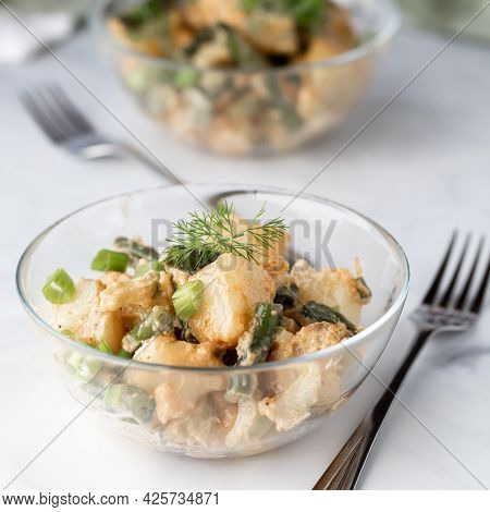 Close Up Of A Bowl Of Creamy Potato Salad Garnished With Dill, Ready For Eating.
